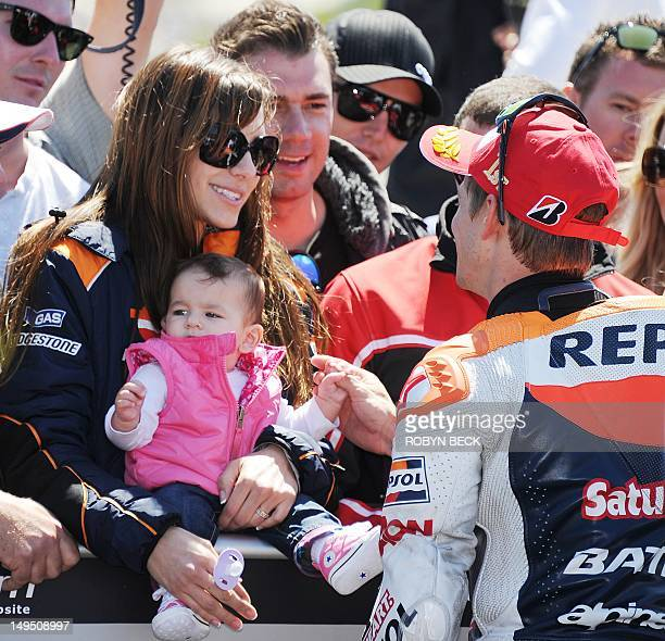 Repsol Honda Team rider Casey Stoner of Australia talks with his wife Adriana Stoner holding their daughter Alessandra Maria after Stoner won the Red...