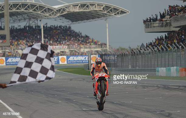 Repsol Honda Team rider Marc Marquez of Spain performs a wheelie as he crosses the finish line during the Malaysian Grand Prix MotoGP motorcycling...