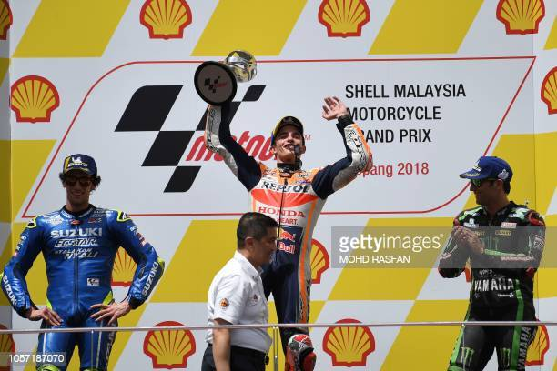 Repsol Honda Team Spanish rider Marc Marquez celebrates on the podium with the trophy after winning the Malaysia MotoGP at the Sepang International...
