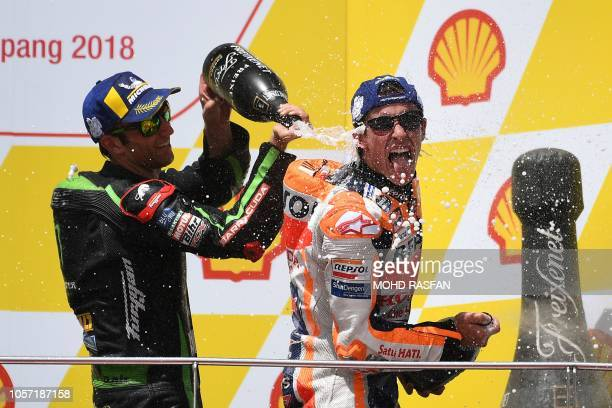 Repsol Honda Team Spanish rider Marc Marquez celebrates on the podium with Monster Yamaha Tech 3 team French rider Johann Zarco after winning the...