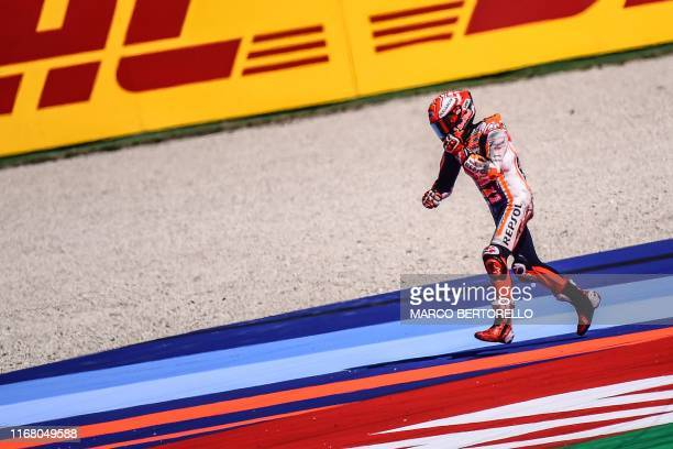 Repsol Honda Team Spanish rider, Marc Marquez runs to pick his motorbike after falling during a free practice session ahead of the San Marino MotoGP...