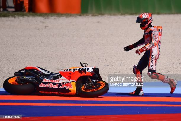 Repsol Honda Team Spanish rider, Marc Marquez runs towards his motorbike after falling during a free practice session ahead of the San Marino MotoGP...