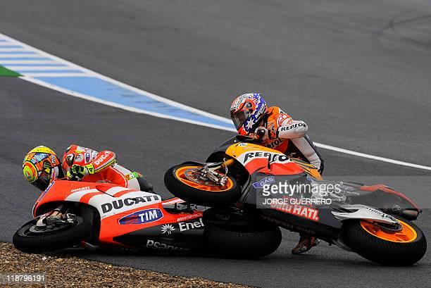 Repsol Honda Team's Australian Casey Stoner and Ducati Team's Italian Valentino Rossi crash during the MotoGP race of the Spanish Prix at Jerez's...