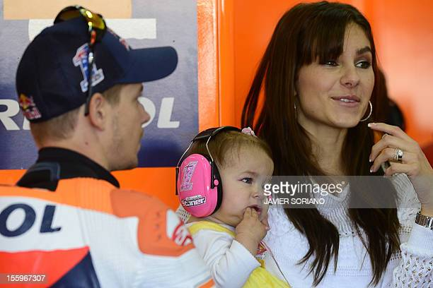Repsol Honda team's Australian rider Casey Stoner his wife Adriana and his daughter Alessandra stand inside the pit during the third MotoGP free...