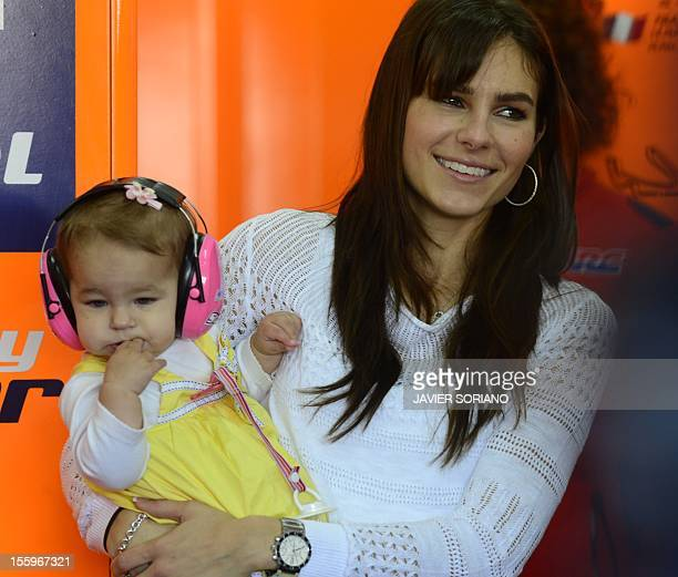 Repsol Honda team's Australian rider Casey Stoner's wife Adriana holds her daughter Alessandra inside the pit during the third MotoGP free practice...