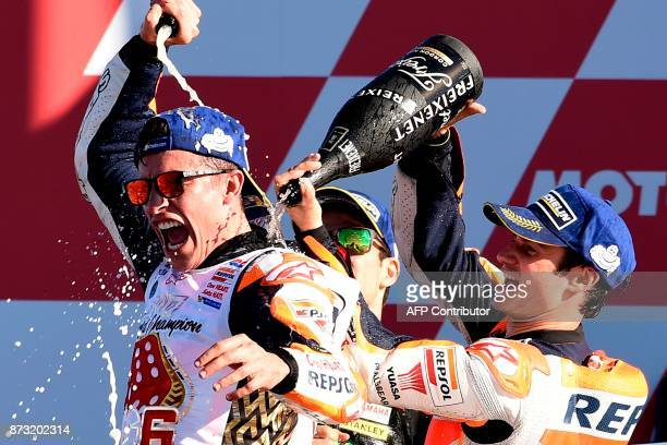 Repsol Honda Team's Spanish rider Dani Pedrosa and Monster Yamaha Tech 3's French rider Johann Zarco spray cava on Repsol Honda Team's Spanish rider...