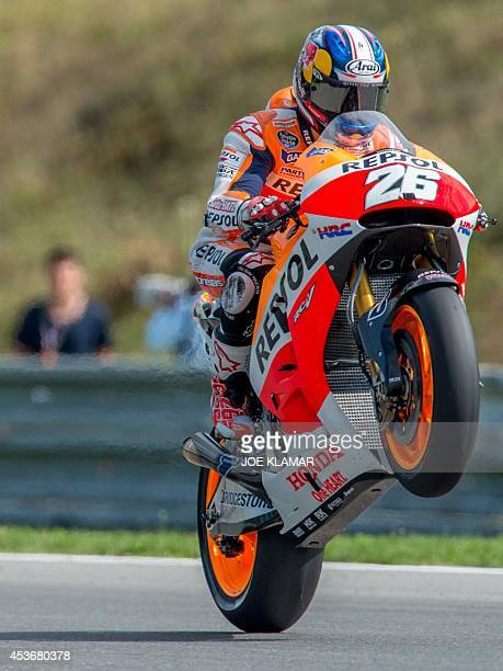 Repsol Honda Team's Spanish rider Dani Pedrosa performs wheelies after the qualification session at the Czech Republic Grand Prix in Moto GP on...