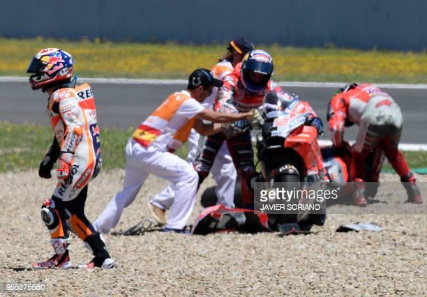 TOPSHOT Repsol Honda Team's Spanish rider Dani Pedrosa walks past Ducati Team's Italian rider Andrea Dovizioso and Ducati Team's Spanish rider Jorge...