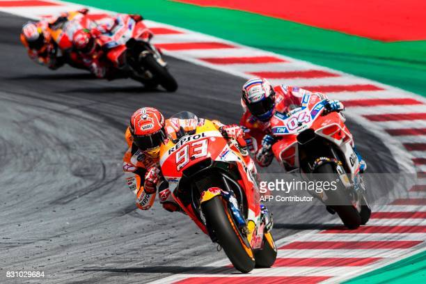 Repsol Honda Team's Spanish rider Marc Marquez and Ducati Team's Italian rider Andrea Dovizioso compete during the MotoGP Austrian Grand Prix race at...