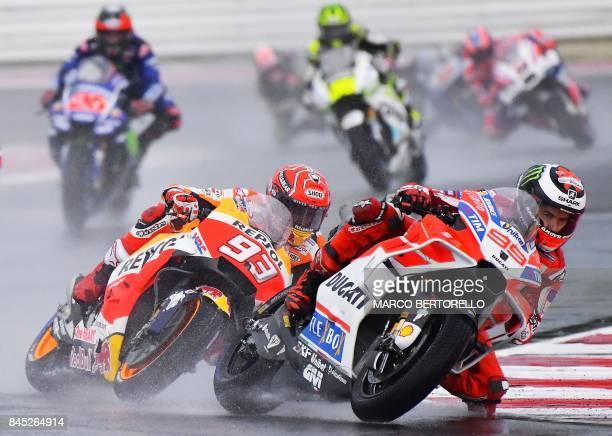 TOPSHOT Repsol Honda Team's Spanish rider Marc Marquez and Ducati Team's Spanish rider Jorge Lorenzo compete during the San Marino Moto GP Grand Prix...