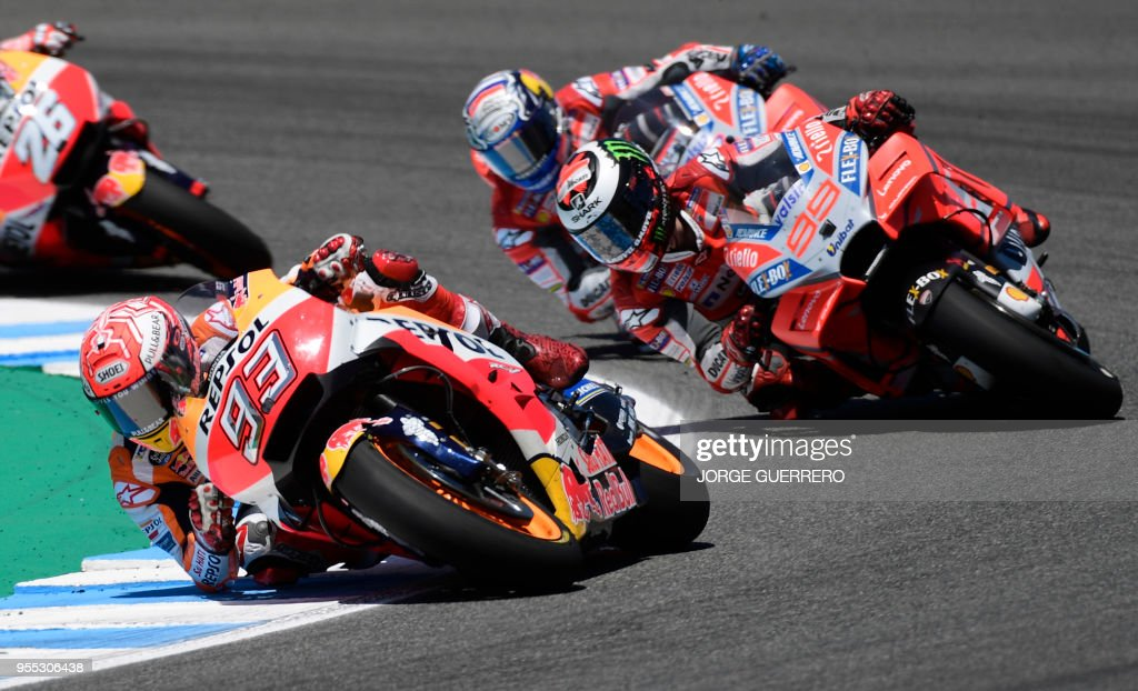 Repsol Honda Team's Spanish rider Marc Marquez (L) and Ducati Team's Spanish rider Jorge Lorenzo (R) compete during the MotoGP race of the Spanish Grand Prix at the Jerez Angel Nieto racetrack in Jerez de la Frontera on May 6, 2018.