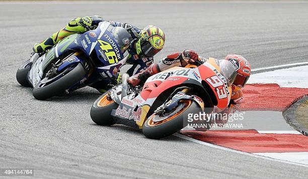 Repsol Honda Team's Spanish rider Marc Marquez and Movistar Yamaha MotoGP's Italian rider Valentino Rossi power their bikes during the 2015 MotoGP...