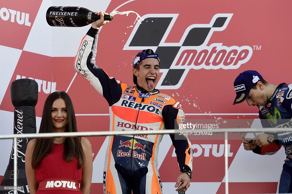 Repsol Honda Team's Spanish rider Marc Marquez (C) and Movistar Yamaha MotoGP's Spanish rider Jorge Lorenzo celebrate on the podium after the MotoGP race of the Motul Comunidad Valenciana Grand Prix at the Ricardo Tormo racetrack in Cheste, on November 13, 2016. / AFP / JAVIER