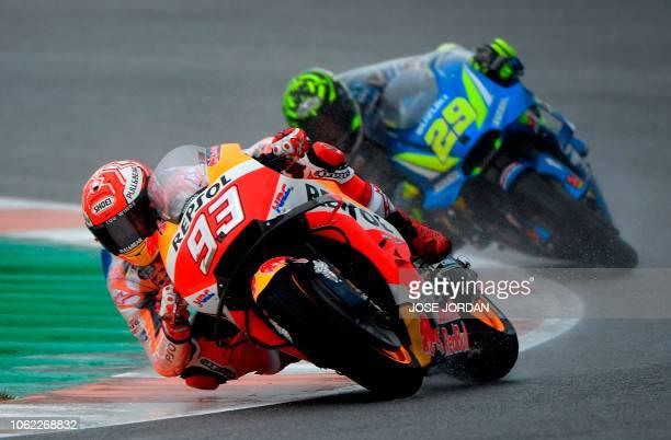 Repsol Honda Team's Spanish rider Marc Marquez and Team SUZUKI ECSTAR's Italian rider Andrea Iannone ride during the first free practice session of...