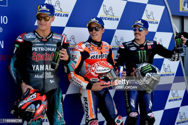 Repsol Honda Team's Spanish rider Marc Marquez celebrates after earning the pole position for tomorrow's race with second placed Petronas Yamaha...