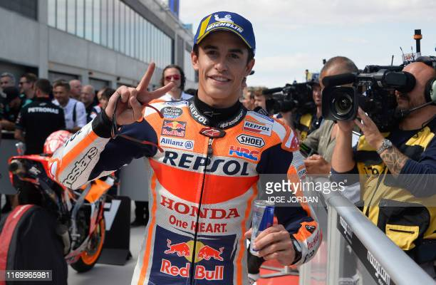 Repsol Honda Team's Spanish rider Marc Marquez celebrates getting the 'pole' position after being first in the MotoGP qualifier of the Aragon Grand...