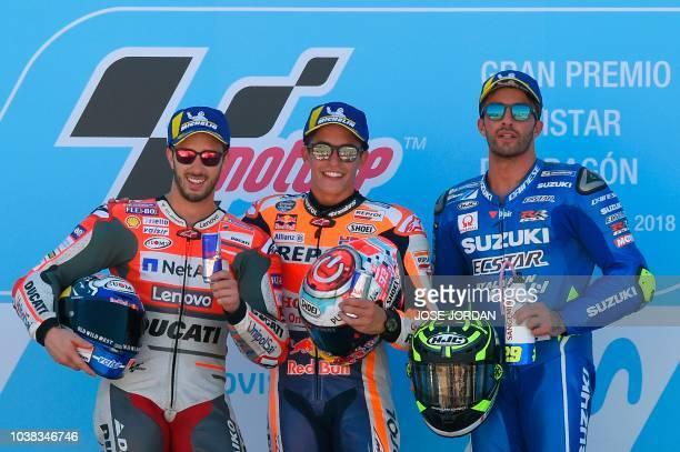 Repsol Honda Team's Spanish rider Marc Marquez celebrates next to Ducati Team's Italian rider Andrea Dovizioso and Team SUZUKI ECSTAR's Italian rider...