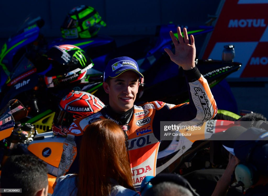 Repsol Honda Team's Spanish rider Marc Marquez celebrates taking the pole position after the second MotoGP qualifying session of the Valencia Grand Prix at Ricardo Tormo racetrack in Cheste, near Valencia on November 11, 2017. /