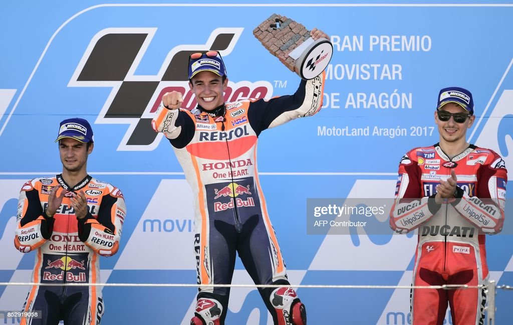 Repsol Honda Team's Spanish rider Marc Marquez (C) celebrates winning on the podium between second placed Repsol Honda Team's Spanish rider Dani Pedrosa (L) and Ducati Team's Spanish rider Jorge Lorenzo after the MOTO GP race of the Moto Grand Prix of Aragon at the Motorland circuit in Alcaniz on September 24, 2017. /