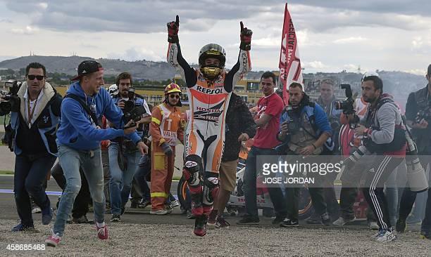 Repsol Honda Team's Spanish rider Marc Marquez celebrates winning the championship after the Valencia Moto Grand Prix at the Ricardo Tormo racetrack...