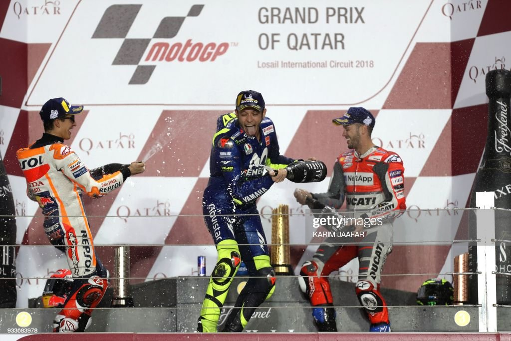 TOPSHOT - Repsol Honda Team's Spanish rider Marc Marquez (L, 2nd place), Ducati Team's Italian rider Andrea Dovizioso (R, 1st place) and Movistar Yamaha MotoGP's Italian rider Valentino Rossi (C, 3rd place) celebrate on the podium following the 2018 Qatar Moto GP Grand Prix at the Losail International Circuit in Lusail, north of Doha, on March 18, 2018. /