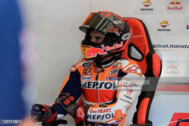 Repsol Honda Team's Spanish rider Marc Marquez gestures while holding his right arm which was operated earlier this week during the fourth MotoGP...
