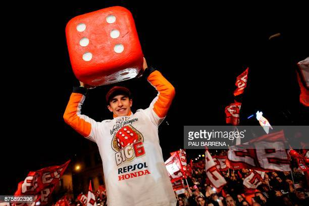 Repsol Honda Team's Spanish rider Marc Marquez holds a big dice as he celebrates his sixth world championship and fourth in the premier MotoGP...