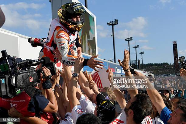 TOPSHOT Repsol Honda Team's Spanish rider Marc Marquez is tossed in the air by team members after winning the MotoGP race at the Japanese Grand Prix...