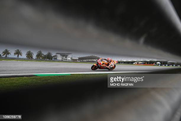 TOPSHOT Repsol Honda Team's Spanish rider Marc Marquez negotiates a corner during the second practice session of the Malaysia MotoGP at the Sepang...