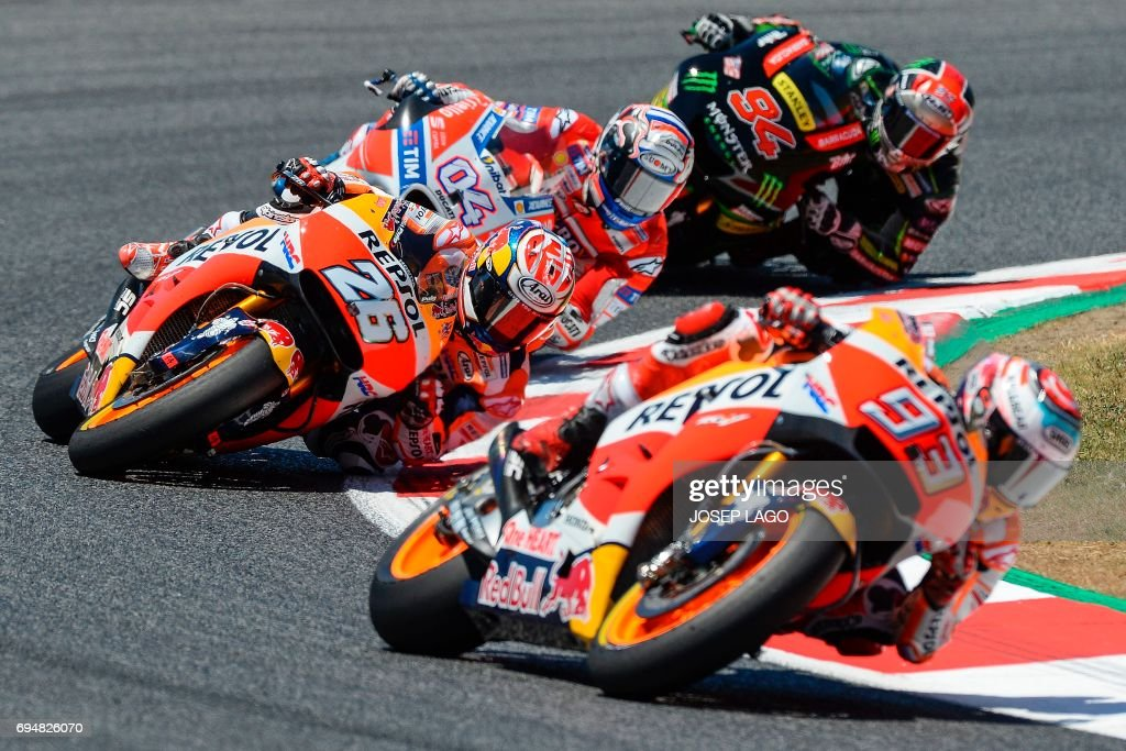 Repsol Honda Team's Spanish rider Marc Marquez, Repsol Honda Team's Spanish rider Dani Pedrosa, Ducati Team's Italian rider Andrea Dovizioso and Monster Yamaha Tech 3's German rider Jonas Folger compete during the Moto GP race of the Catalunya Grand Prix at the Montmelo racetrack near Barcelona on June 11, 2017. / AFP PHOTO / Josep LAGO