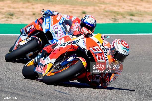 TOPSHOT Repsol Honda Team's Spanish rider Marc Marquez rides in front of Ducati Team's Italian rider Andrea Dovizioso during MotoGP race of the Moto...