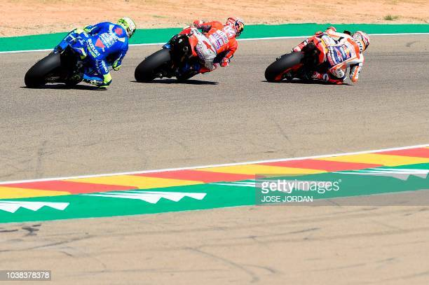 Repsol Honda Team's Spanish rider Marc Marquez rides in front of Ducati Team's Italian rider Andrea Dovizioso and Team SUZUKI ECSTAR's Italian rider...