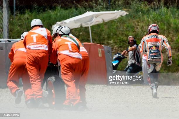 Repsol Honda Team's Spanish rider Marc Marquez runs after crashing during the fourth MotoGP free practice session of the Moto Grand Prix de Catalunya...