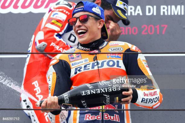 Repsol Honda Team's Spanish rider Marc Marquez sprays champagne as he celebrates on the podium after winning the San Marino Moto GP Grand Prix at the...