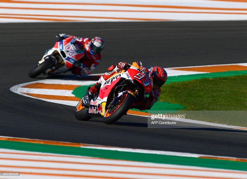 Repsol Honda Team's Spanish rider Marc Marquez takes a curve followed by Ducati Team's Italian rider Andrea Dovizioso during the third MotoGP free practice session of the Valencia Grand Prix at Ricardo Tormo racetrack in Cheste, near Valencia on November 11, 2017. /