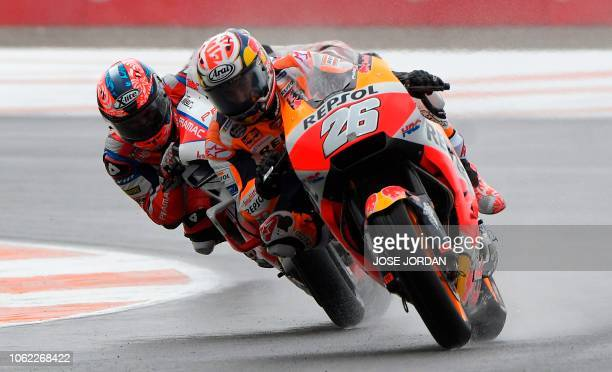 TOPSHOT Repsol Honda's Spanish rider Dani Pedrosa and Alma Pramac Racing Italian rider Danilo Petrucci ride during the first free practice session of...