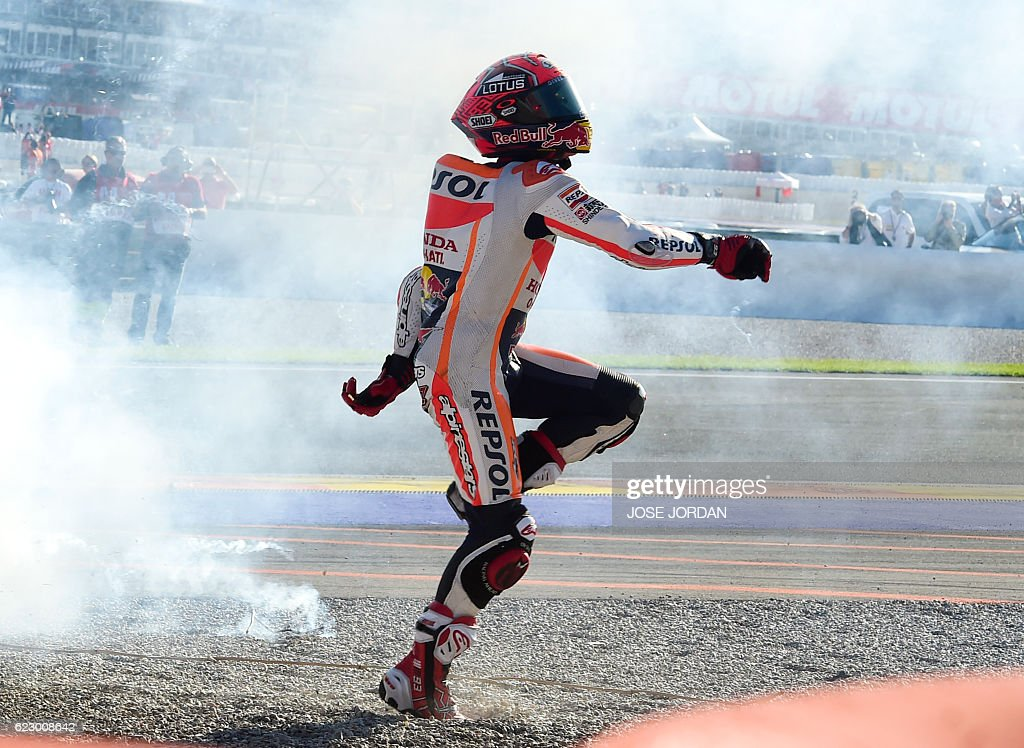Repsol Honda's Spanish rider Marc Marquez celebrates after the Moto GP race of the Motul Comunidad Valenciana Grand Prix at the Ricardo Tormo racetrack in Cheste, on November 13, 2016. / AFP / Jose Jordan