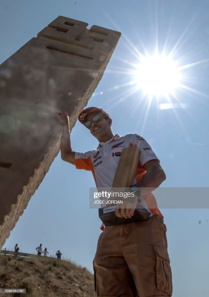 Repsol Honda's Spanish rider Marc Marquez poses next to a monolith inaugurated on September 20, 2018 at the Motorland racetrack in Alcaniz and placed at a curve named after the rider.