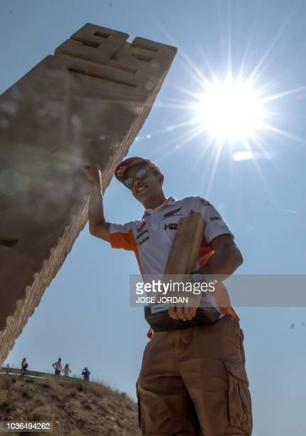 Repsol Honda's Spanish rider Marc Marquez poses next to a monolith inaugurated on September 20, 2018 at the Motorland racetrack in Alcaniz and placed...