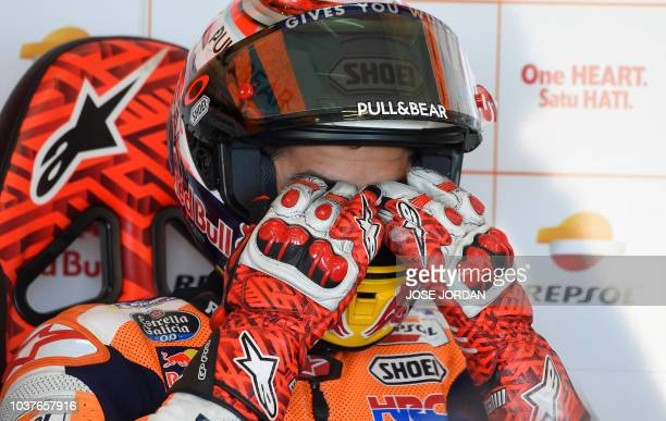 Repsol Honda's Spanish rider Marc Marquez rubs his eyes as he sits in the box during the MotoGP fourth free practice of the Aragon Grand Prix at the...