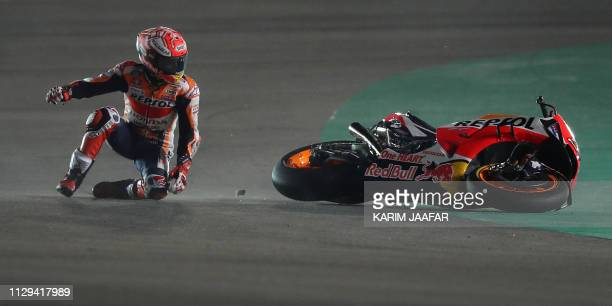 Repsol rider and current world champion Marc Marquez of Spain tries to get up after crashing in the fourth free practice session at Losail track near...