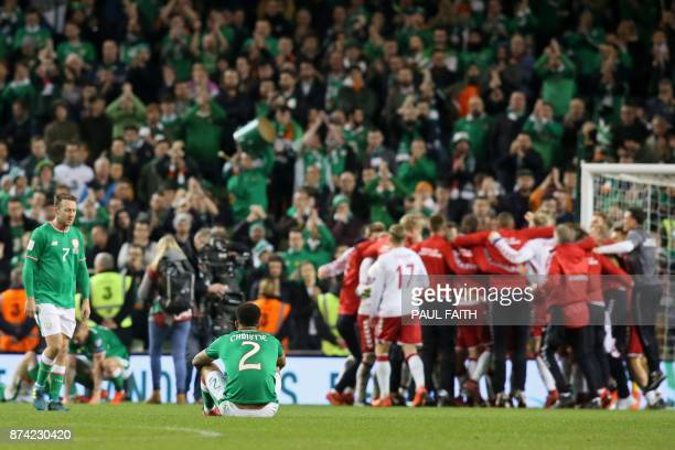 Republic of Ireland players react to their defeat as denmark players celebrate on the pitch after the FIFA World Cup 2018 qualifying football match...