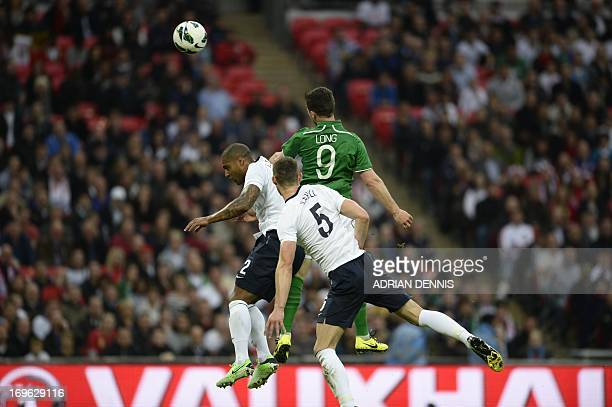 Republic of Ireland striker Shane climbs above England defender Glen Johnson and England defender Gary Cahill to head in the opening goal during the...