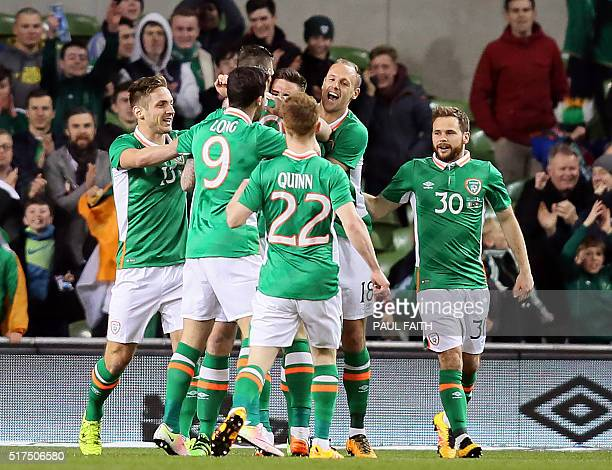 Republic of Ireland's defender Ciaran Clark celebrates with teammates after scoring his early opening goal in the friendly football match between...