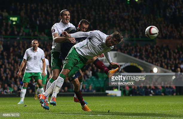 Republic of Ireland's defender Richard Keogh heads the ball clear of Scotland's striker Steven Fletcher during the Euro 2016 Qualifier Group D...