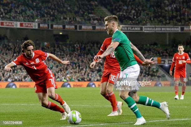Republic of Ireland's midfielder Jeff Hendrick runs at Wales' midfielder Joe Allen during the UEFA Nations League football match between Republic of...