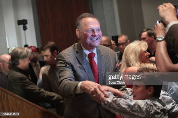 Republican candidate for the US Senate in Alabama Roy Moore greets supporters at an electionnight rally on September 26 2017 in Montgomery Alabama...