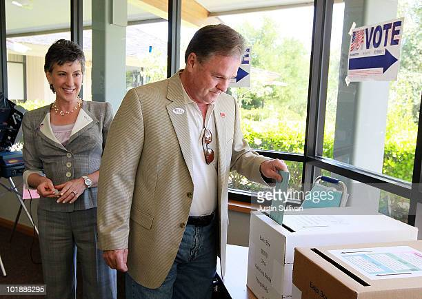 Republican candidate for US Senate and former HP CEO Carly Fiorina looks on as her husband Frank Fiorina casts his ballot at a polling place June 8...