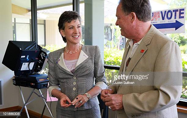 Republican candidate for US Senate and former HP CEO Carly Fiorina smiles with her husband Frank Fiorina after casting their ballots at a polling...