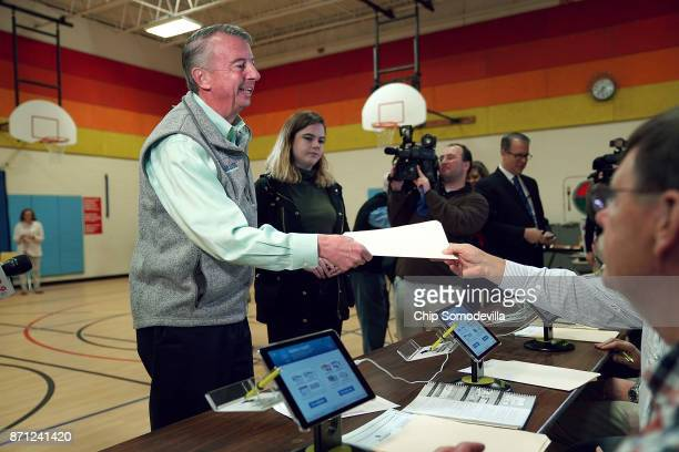 Republican candidate for Virginia governor Ed Gillespie receives his ballot while voting in the gymnasium at Washington Mill Elementary School...